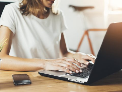 woman typing on laptop at desk how to set up a home workspace