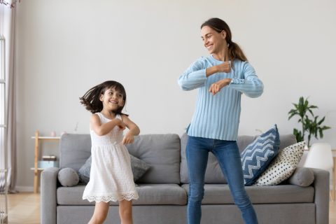 mother and daughter dancing in living room ways to exercise without a gym BodyViva