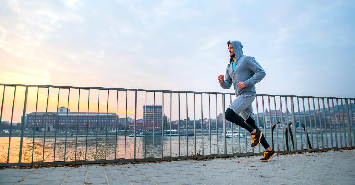"""alt=""""man running in the cold along river"""""""