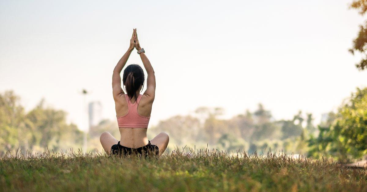 "alt=""Woman doing yoga in a park"""